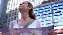 Close-up of beautiful woman tourist looking at map in Times Square American Flag Stock Footage