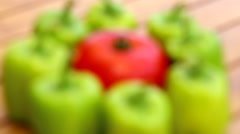 Focusing on a wet red tomatoes closeup in the middle of green bell pepper Stock Footage