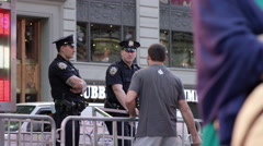 Police officers behind police barrier helping man Time Square day NYPD NYC Stock Footage