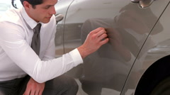 Businessman checking the cars paint job Stock Footage