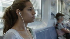 Serious looking woman with ponytail riding elevated subway train wearing earbuds Stock Footage