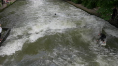 Surfing on a white surfboard, on Isar River, Munich - stock footage