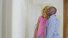 4K Happy attractive mixed ethnicity couple painting a wall in new home - stock footage