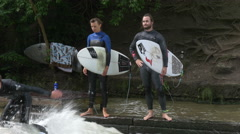 Surfers holding their surfboards and waiting on the riverside in Munich Stock Footage
