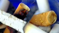 Macro view of burning cigarette and stubs with the smoke in ashtray Stock Footage