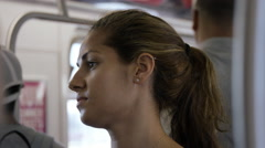 Profile beautiful woman's face riding crowded subway train commuting NYC 4K Stock Footage
