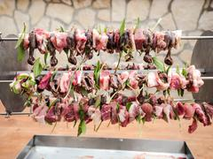 Birds on the spit with meat, bacon and sage ready to be cooked Stock Photos