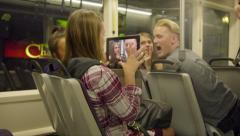 Teens taking pictures with iPad on Max train Stock Footage