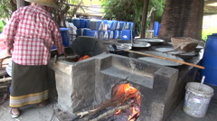 Making Fruit Drink - A fire burns under the large pans Stock Footage