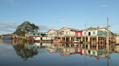 Riverside houses in the amazon river at the board of Brazil, Peru and Colombia. - stock footage