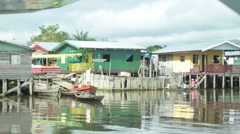 Riverside houses in the amazon river at the board of Brazil, Peru and Colombia. Stock Footage