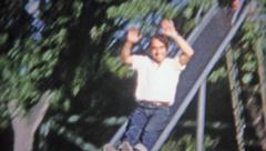 1952: Dad going down slide like daughters do. Stock Footage