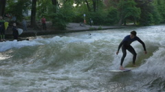 Two men river surfing in Munich Stock Footage