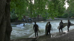 Four surfers waiting on the riverside in the English Garden, Munich Stock Footage