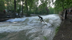 Young man surfing on Isar River, Munich Stock Footage