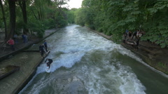 One man surfing and two other waiting on the riverside in Munich Stock Footage