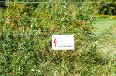 Electric fence with warning sign to prevent shock Stock Photos