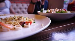 Friends dinner with seafood spaghetti foreground Stock Footage