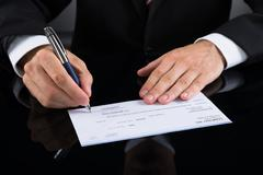 Close-up Of Businessperson Hands Signing Cheque With Pen - stock photo