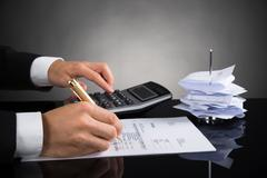 Close-up Of Businessperson Calculating Invoice With Calculator At Desk Stock Photos