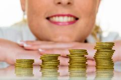 Save woman with stack of coins in money Stock Photos