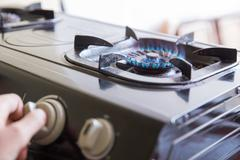 Stock Photo of Hand switching a knop on a stove, close up