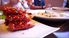 Friends dinner with Korean spicy chicken wing foreground Stock Footage