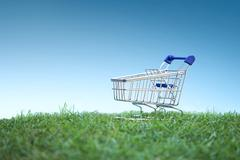 Stock Photo of Trolley on green grass, Green Shopping concept