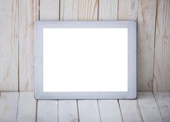 Tablet pc on the wall and wooden background, mock up - stock photo
