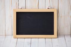 Stock Photo of Black chalkboard hanging on wooden dark background, horizontally placed