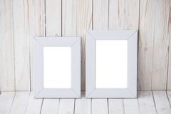 Stock Photo of Two kind sizes of white frame on wooden background