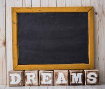 Chalkboard and DREAMS sign made of wooden blocks on wooden background - stock photo