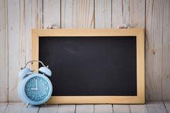 Stock Photo of Chalkboard and blue alarm clock on wooden background