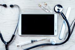 Tablet pc with medical objects on a desk as a metaphor for electronic diagnostic - stock photo