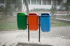 Stock Photo of Three trash bin in different colors on a park