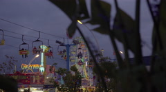 Amusement park and rides on a cloudy early evening. 4K UHD. Stock Footage