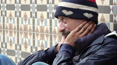 Asiatic homeless waiting for charity: poor man in the street asking for food - stock footage