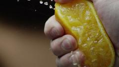 Hand squeezes orange slow motion - stock footage