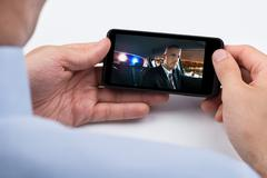 Close-up Of Person Watching Video On Mobile Phone Stock Photos