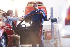 Mechanic and customer in car handshaking in auto repair shop Stock Photos