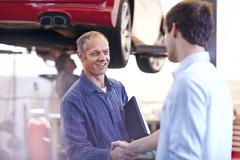 Mechanic and customer handshaking in auto repair shop Stock Photos