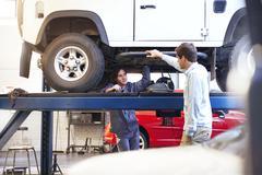 Mechanic under car talking to customer in auto repair shop Stock Photos