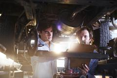 Mechanics with clipboard under car in auto repair shop Stock Photos
