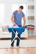 Young Happy Man Ironing Clothes On Ironing Board Stock Photos
