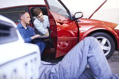 Mechanics with laptop talking at car in auto repair shop - stock photo