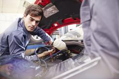Mechanic working on car engine in auto repair shop Stock Photos
