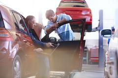 Mechanic with laptop talking to customer at car in auto repair shop Stock Photos
