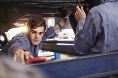 Mechanic reaching for tool in auto repair shop - stock photo