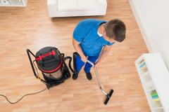 High Angle View Of Male Janitor Cleaning Floor With Vacuum Cleaner - stock photo
