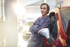 Portrait confident mechanic leaning on car in auto repair shop Stock Photos